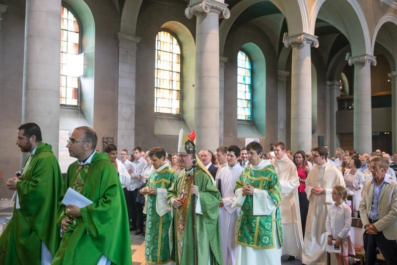 Mgr Charles Morerod, évêque diocésain, entre dans la basilique de Lausanne, entouré des prêtres participant à l'ordination. © J-P Gadmer