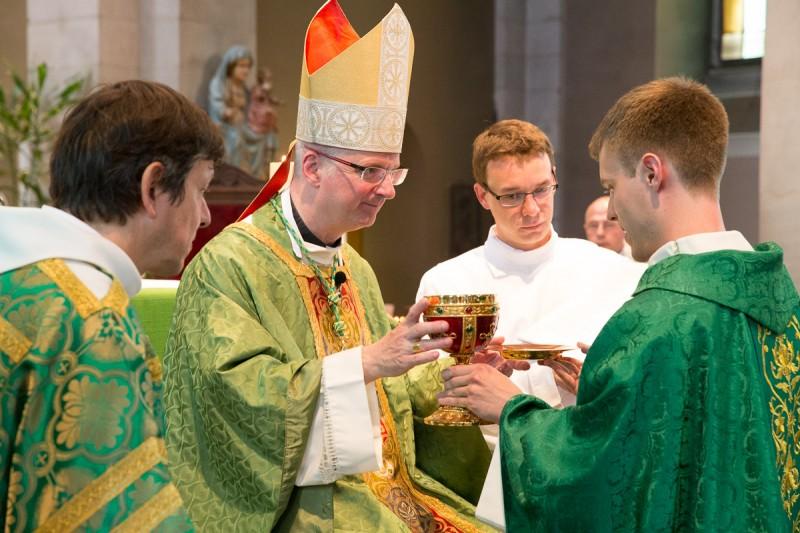 L'abbé Burin des Roziers remet le calice à Mgr Morerod pour la consécration. © J-P Gadmer