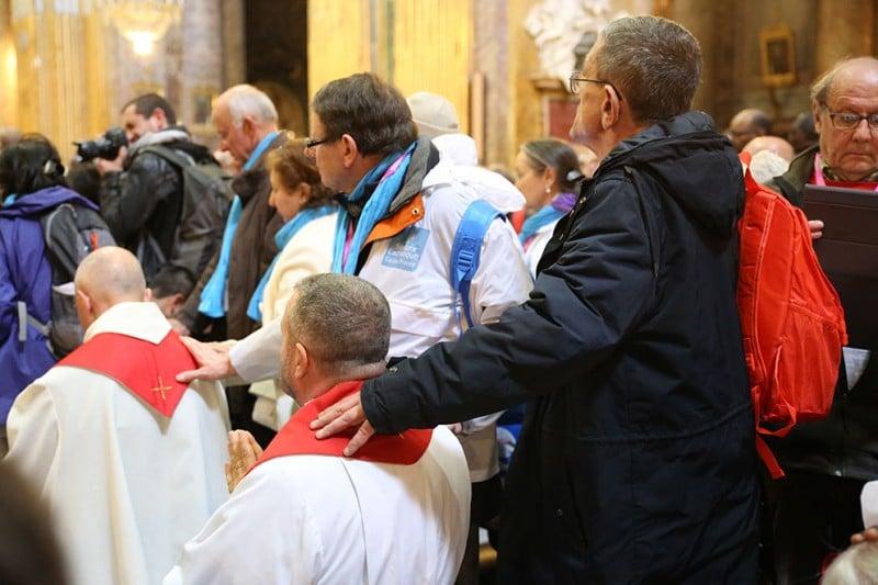 Les prêtres sont à genoux à la fin de la célébration. Les pèlerins posent leur main sur leur épaule et prient pour eux.